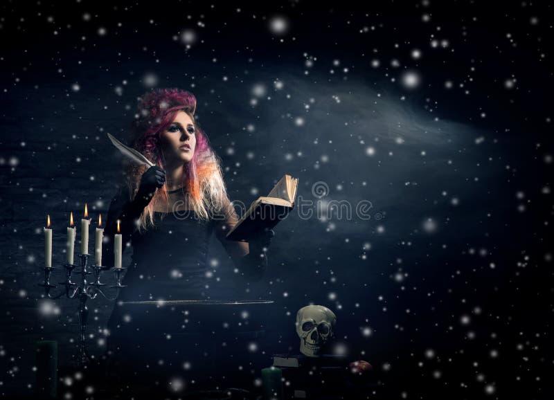 Красивая ведьма делая колдовство в подземелье стоковое фото