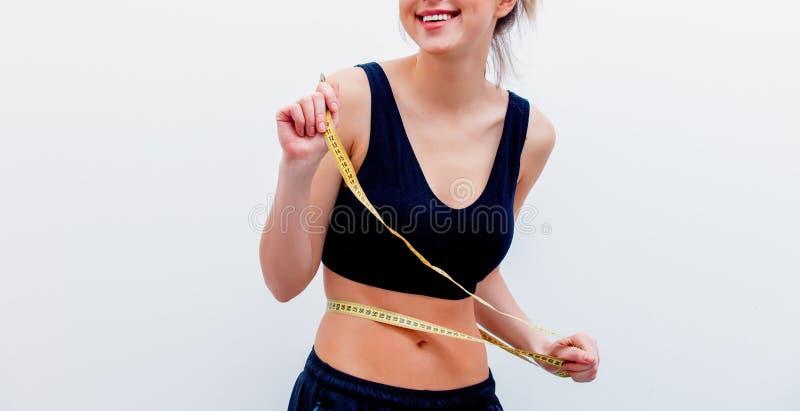 Красивая взрослая лента измерения удерживания девушки спорта стоковое изображение rf