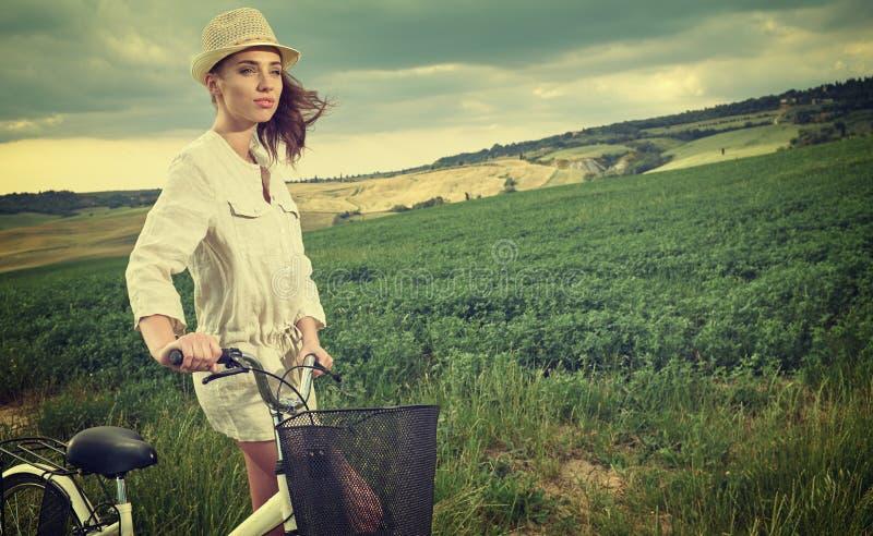 Красивая винтажная девушка сидя рядом с велосипедом, летом стоковые фотографии rf