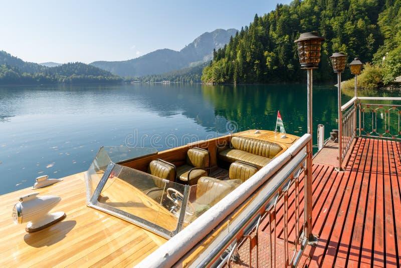 Красивая винтажная шлюпка скорости причаливает на пристани на озере Ritsa Взгляд кормовой части шлюпки стоковые изображения