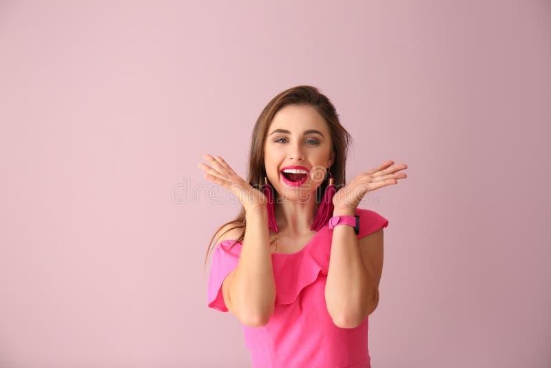 Красивая возбужденная молодая женщина на предпосылке цвета стоковое фото rf