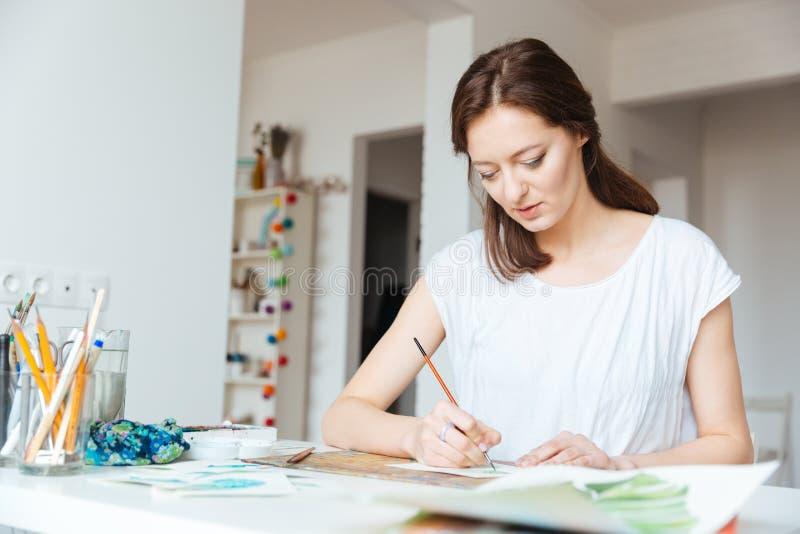 Красивая воодушевленная картина художника женщины в студии искусства стоковые фотографии rf