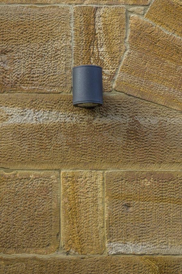 Красивая восстановленная и взорванная стена песчаника с современной цвета антрацит лампой металла стоковые изображения rf