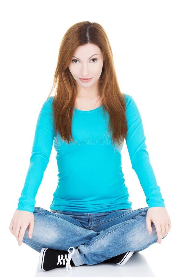 Красивая вскользь женщина сидя и держа ее колени. стоковое фото rf