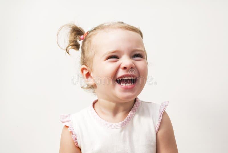 Красивая выразительная прелестная счастливая милая смеясь над усмехаясь сторона младенца младенца стоковая фотография
