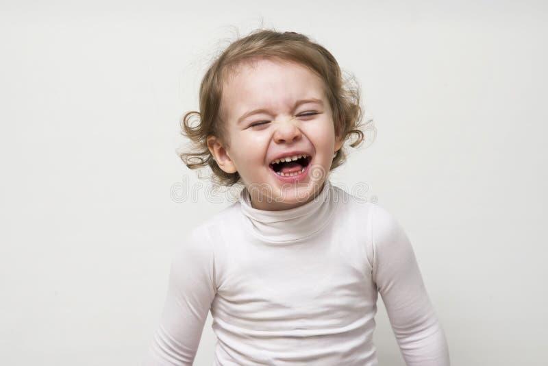 Красивая выразительная счастливая милая смеясь над усмехаясь сторона младенца младенца стоковое фото