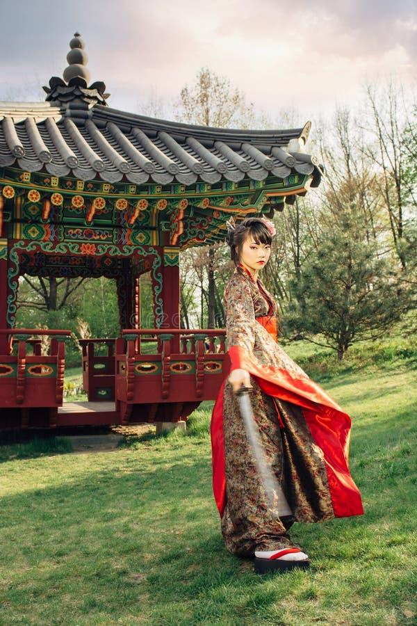 Красивая гейша в кимоно с шпагой самураев стоковые изображения rf