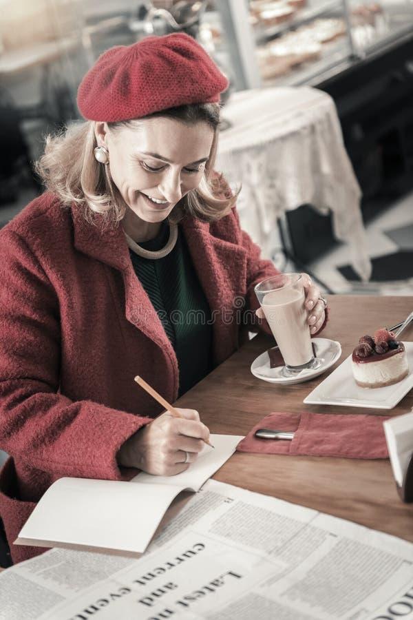 Красивая дама писать стихотворение в ее тетрадь с прописями стоковые фото