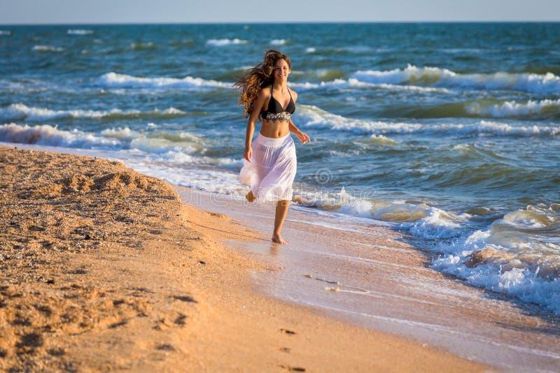Красивая девушка бежать на прибое стоковые изображения