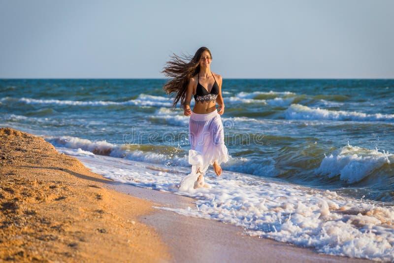 Красивая девушка бежать на прибое стоковое изображение rf