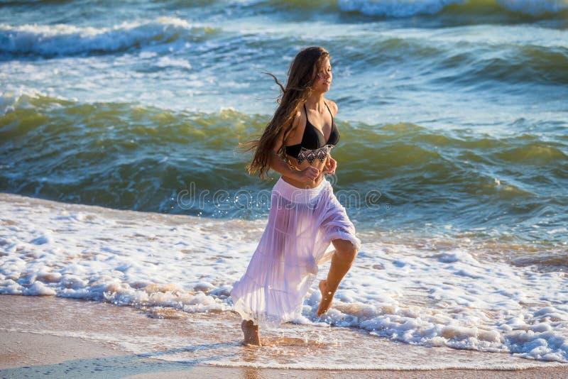 Красивая девушка бежать на прибое стоковые фото