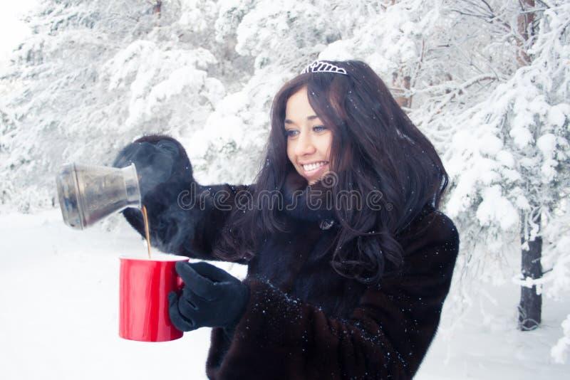Красивая девушка брюнет в меховой шыбе на предпосылке леса зимы, льет горячий кофе от турков в красной чашке стоковая фотография rf
