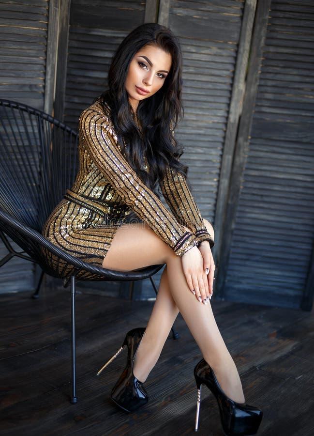 Красивая девушка брюнет в сексуальном коротком платье стоковое фото
