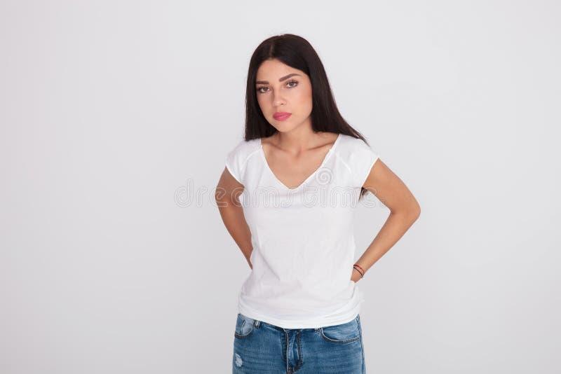 Красивая девушка брюнет нося белое положение футболки стоковая фотография rf