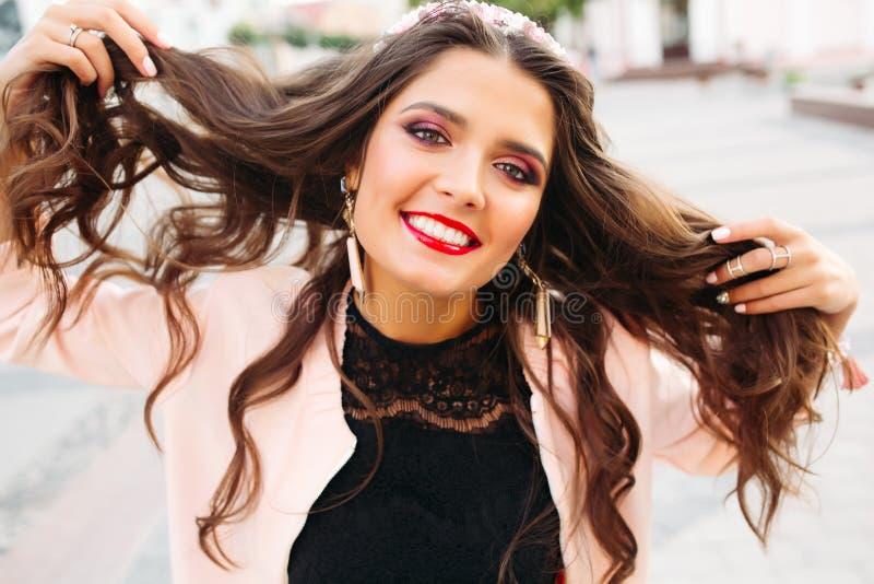 Красивая девушка брюнет с яркой составляет держать ее волосы и усмехаться на камере стоковые изображения rf