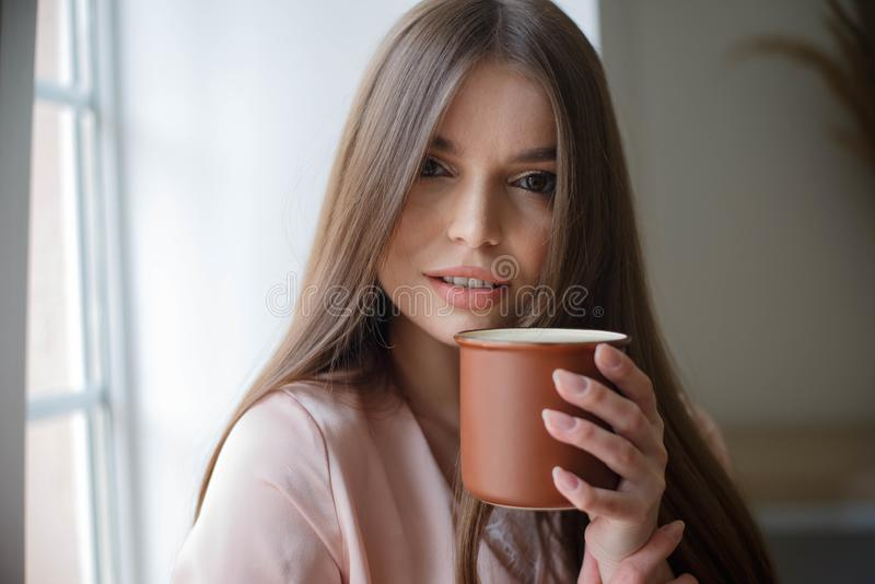 Красивая девушка выпивает кофе и усмехаясь промежуток времени сидя на кафе стоковая фотография