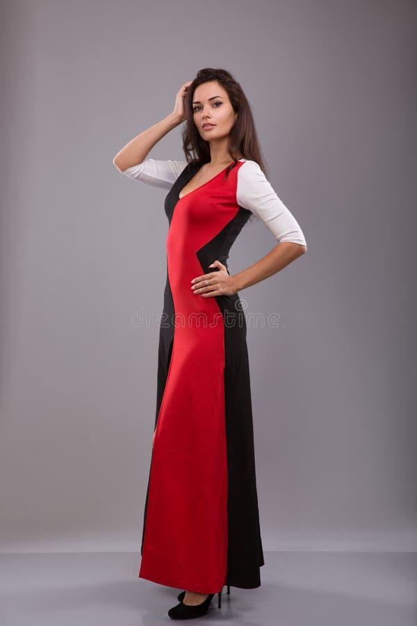 Красивая девушка выравнивая длинное платье представляя против серой предпосылки стоковое изображение rf
