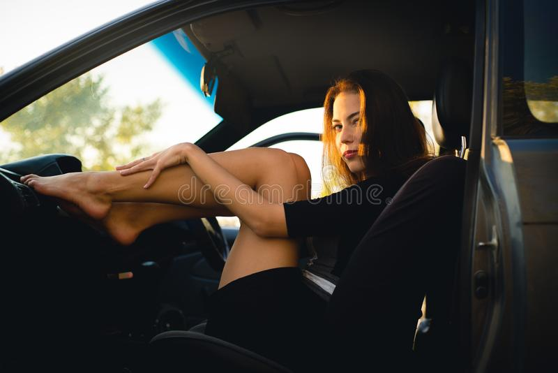 Красивая девушка в автомобиле положила ее ноги на панель стоковая фотография rf