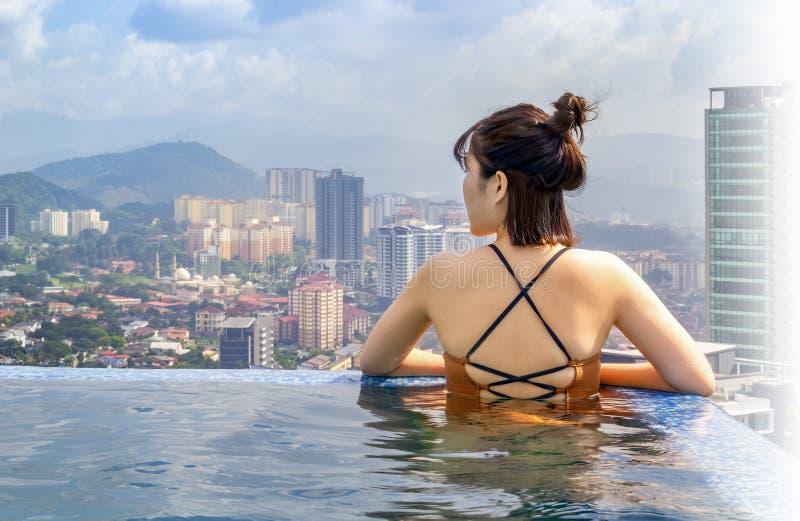 Красивая девушка в бассейне на крыше здания восхищает взгляды города стоковое фото rf
