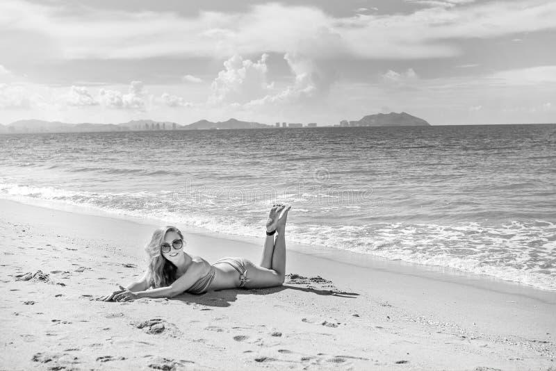 Красивая девушка в бикини представляя на дезертированном пляже белый песок, море бирюзы и маленькая девочка стоковые изображения rf