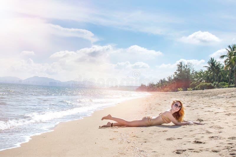 Красивая девушка в бикини представляя на дезертированном пляже белый песок, море бирюзы и маленькая девочка стоковое фото rf