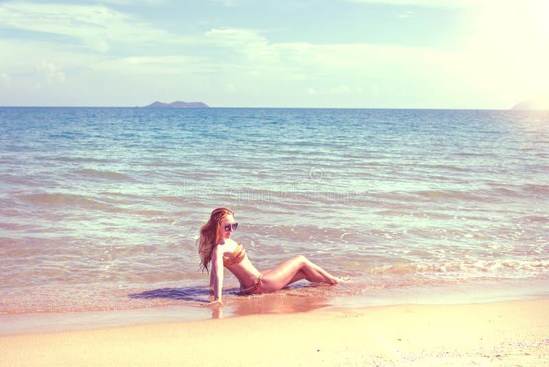 Красивая девушка в бикини представляя на дезертированном пляже белый песок, море бирюзы и маленькая девочка стоковая фотография