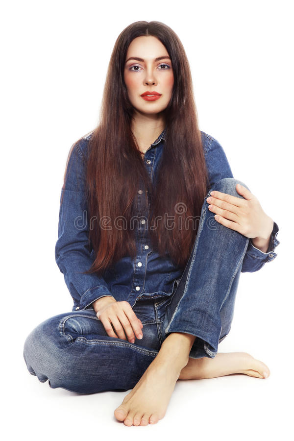 Красивая девушка в джинсах сидя над белой предпосылкой стоковое фото