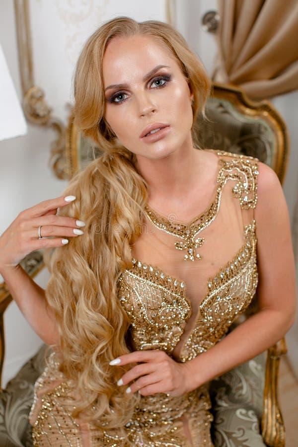 Красивая девушка в длинном платье золота стоковая фотография