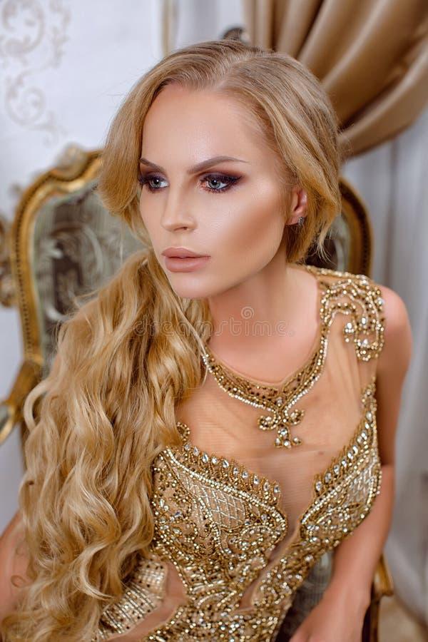 Красивая девушка в длинном платье золота стоковая фотография rf