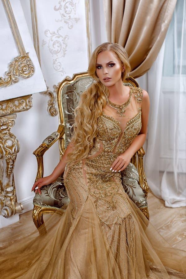 Красивая девушка в длинном платье золота стоковое фото rf