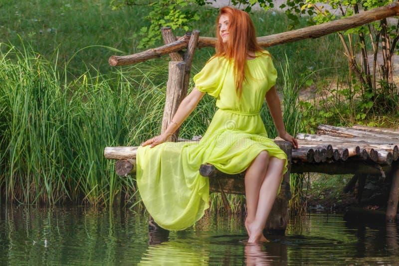Красивая девушка в желтом платье на речном береге стоковые фотографии rf