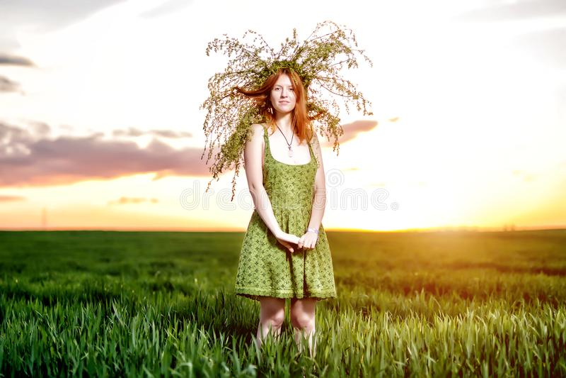 Красивая девушка в зеленом платье с венком положения цветков стоковое фото