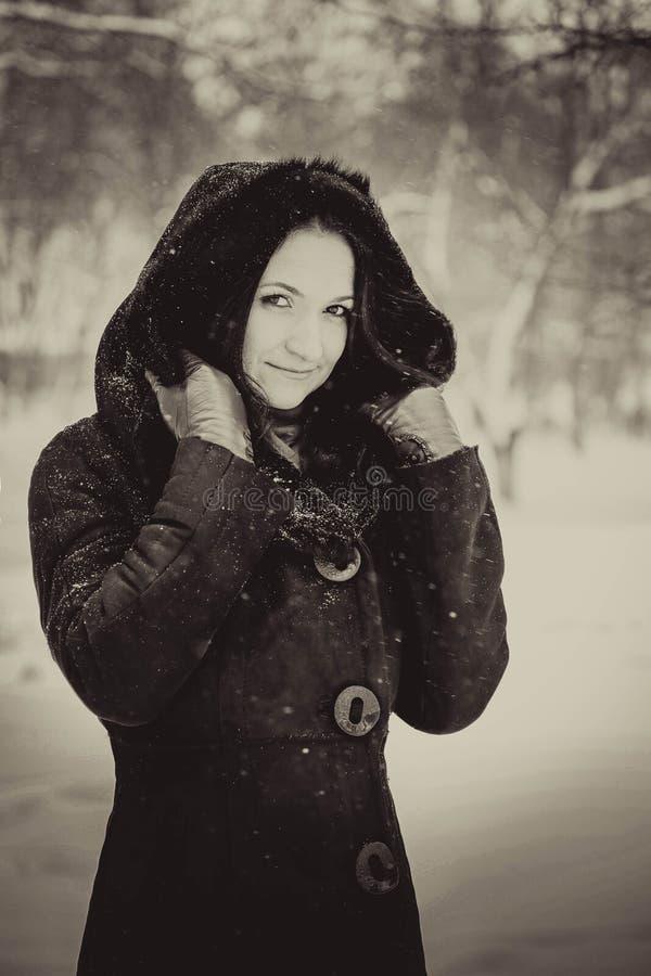 Красивая девушка в клобуке пряча от снега стоковое изображение rf