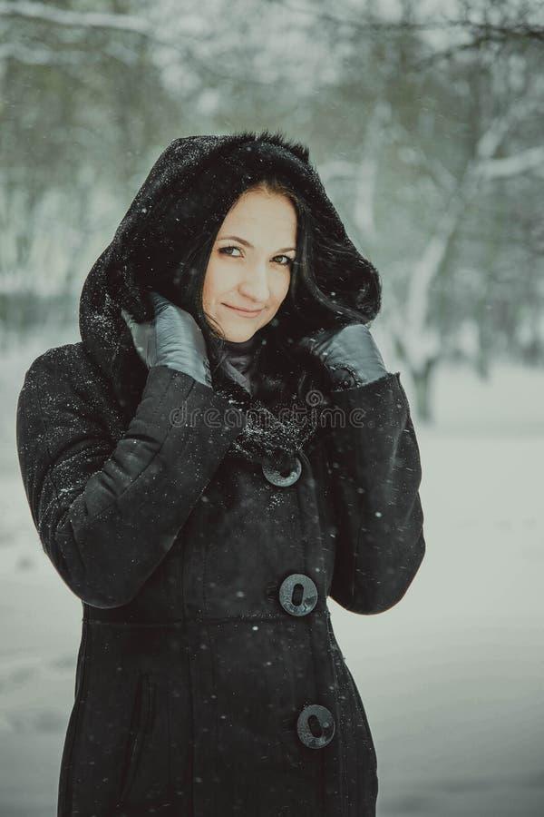 Красивая девушка в клобуке пряча от снега стоковые фото