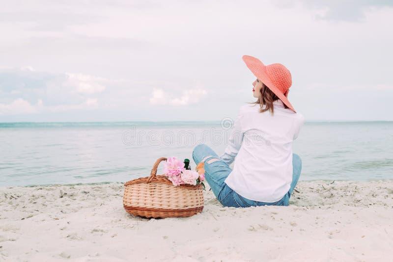 Красивая девушка в красной шляпе с корзиной пикника на портовом районе лета стоковая фотография rf