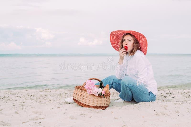 Красивая девушка в красной шляпе с корзиной пикника на портовом районе лета стоковые изображения
