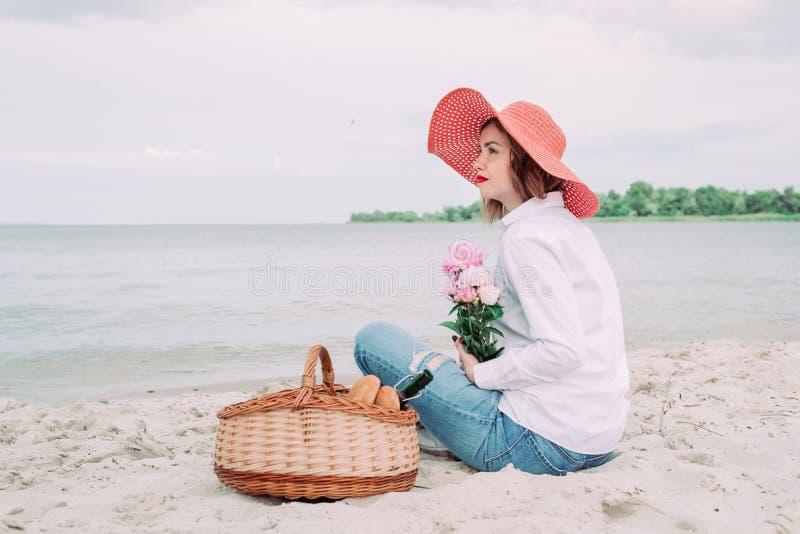 Красивая девушка в красной шляпе с корзиной пикника на портовом районе лета стоковые фото