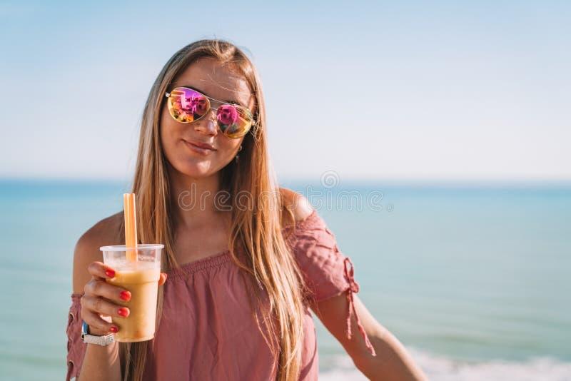 Красивая девушка в красочные солнечные очки выпивая коктеиль стоковые фотографии rf