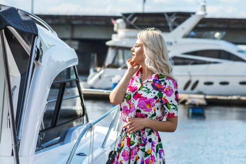Красивая девушка в платье стойка на пристани против фона яхт в лете стоковое изображение