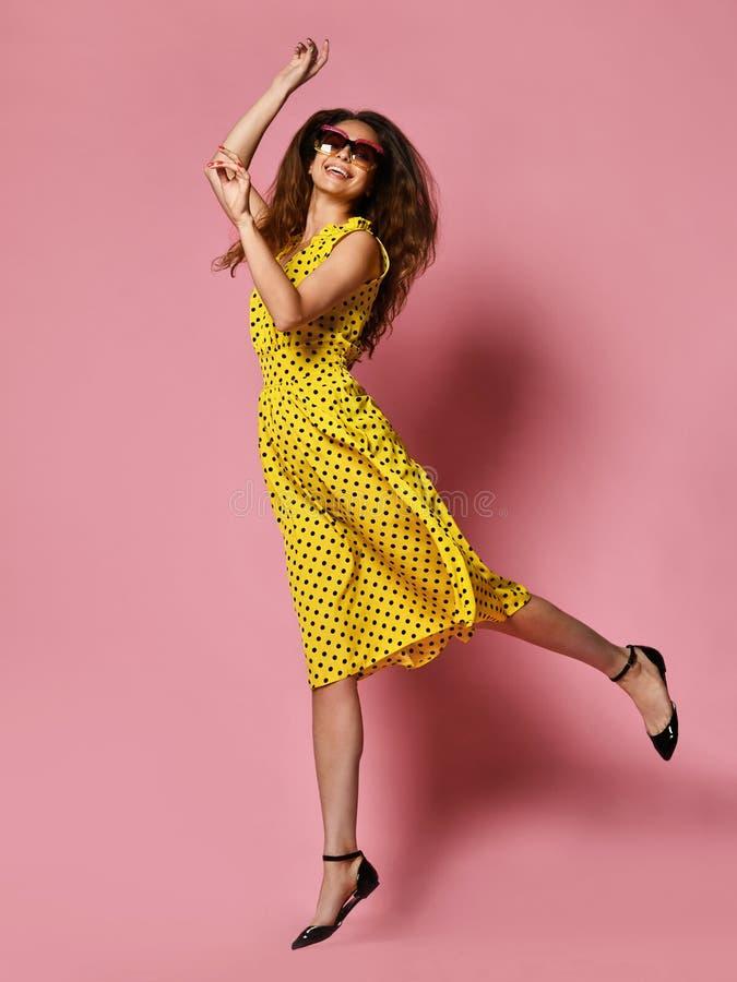 Красивая девушка в романтичном платье усмехаясь довольно на пурпурной предпосылке Худенькая курчавая женская модель в желтом плат стоковое фото rf