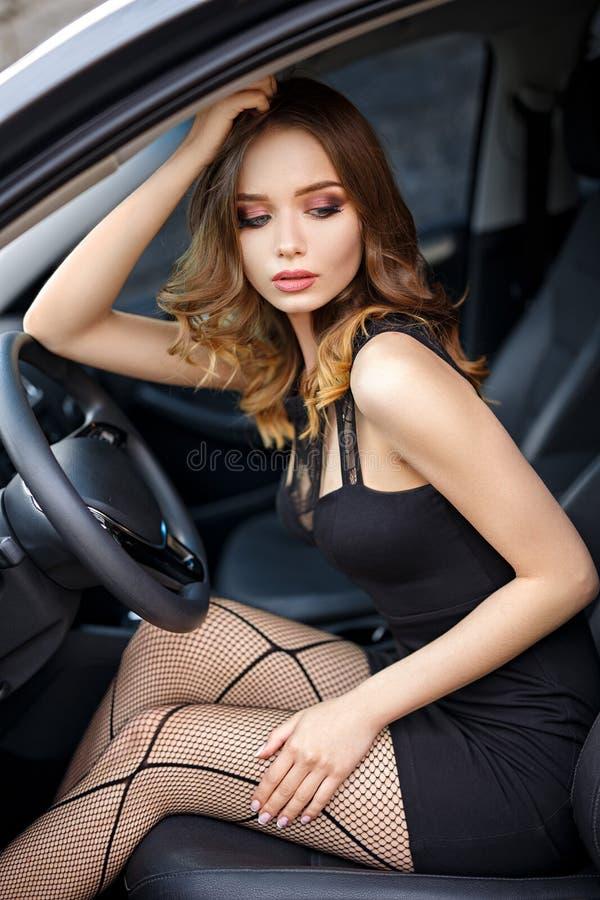 Красивая девушка в сексуальном платье в современном автомобиле стоковые изображения