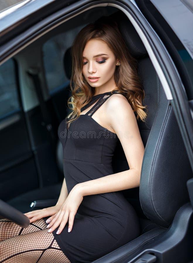 Красивая девушка в сексуальном платье в современном автомобиле стоковая фотография