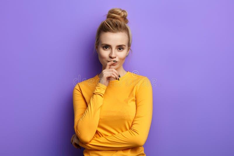 Красивая девушка в случайных одеждах держа руку на подбородке в сомнении стоковое фото