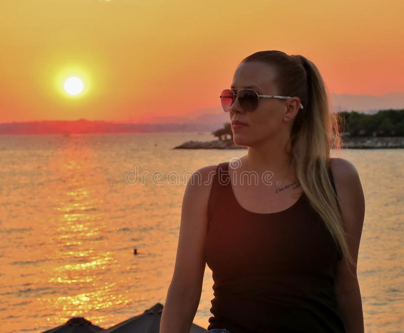 Красивая девушка в стеклах на заходе солнца в Европе стоковое фото rf