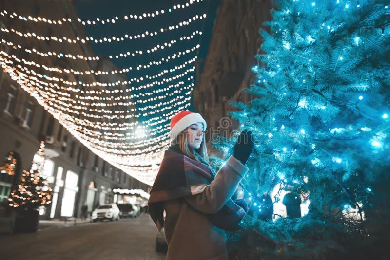 Красивая девушка в теплых одеждах и шляпе рождества стоит вечером на дерев-дереве на украшенной улице стоковое изображение rf