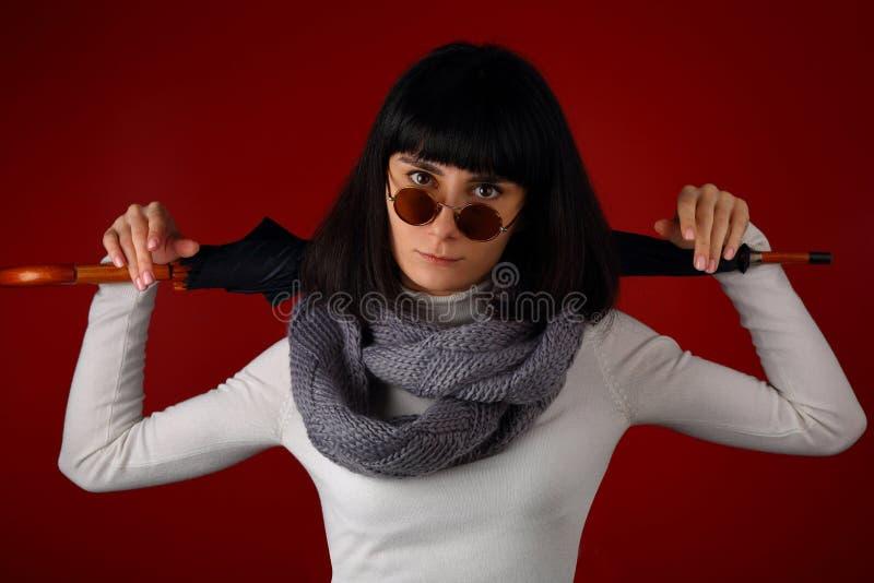 Красивая девушка в шарфе и ретро стеклах с зонтиком стоковая фотография