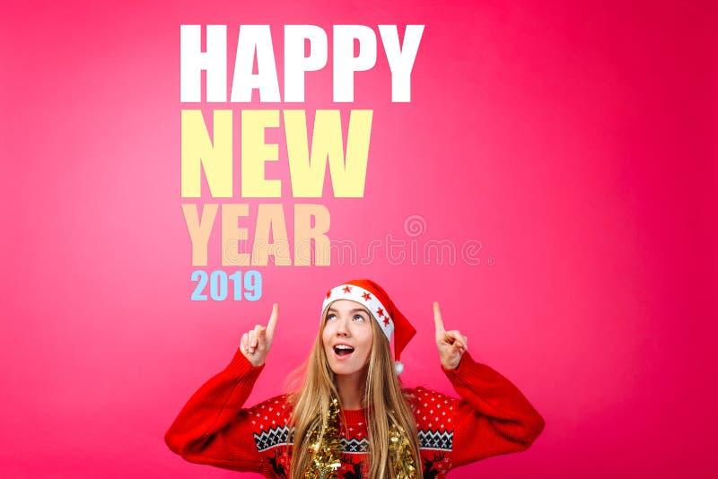 Красивая девушка в шляпе Санта, с сусалью вокруг ее шеи, указывая пальцы вверх и показывая пустое пространство с текстом Счастлив стоковое изображение rf