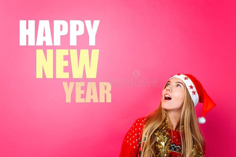 Красивая девушка в шляпе Санта, с сусалью вокруг ее шеи, указывая пальцы вверх и показывая пустое пространство с текстом Счастлив стоковая фотография rf