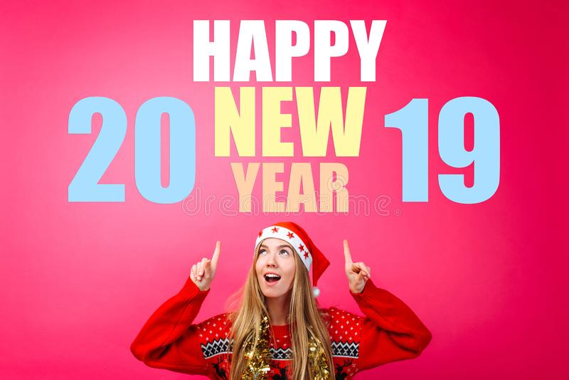 Красивая девушка в шляпе Санта, с сусалью вокруг ее шеи, указывая пальцы вверх и показывая пустое пространство с текстом Счастлив стоковые фото