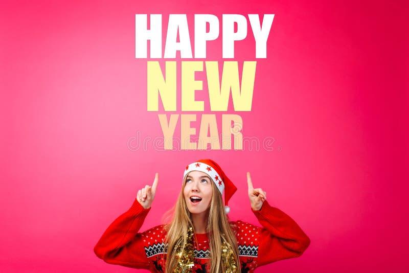 Красивая девушка в шляпе Санта, с сусалью вокруг ее шеи, указывая пальцы вверх и показывая пустое пространство с текстом Счастлив стоковые изображения